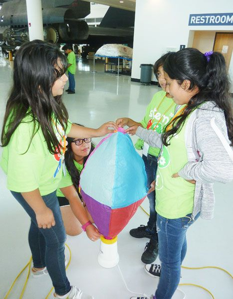 Starla Pointer / News-Register##Daniela Anaya, second from left, holds the balloon s neck against a hot air popper and Hannia Pacheco, Diana Alba and Angela Landeros steady the envelope as it fills with air, causing lift.