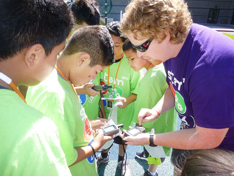 Starla Pointer / News-Register##Teacher David Larson shows Aaron Melcher and other students how to use a GPS tracking device before they set off to find clues left by the Cheeto bandit.