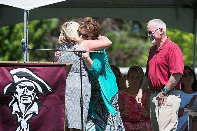 Marcus Larson/News-Register##At the 2015 Dayton High School graduation, Superintendent Janelle Beers hugs retired teacher Debbie Kearns as Cal Kearns waits his turn. The couple were named Dayton Education Citizens of the Year.