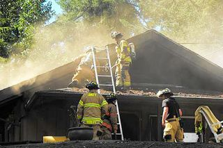 Submitted photo##Firefighters battle a blaze at a rural Willamina home caused by fireworks.