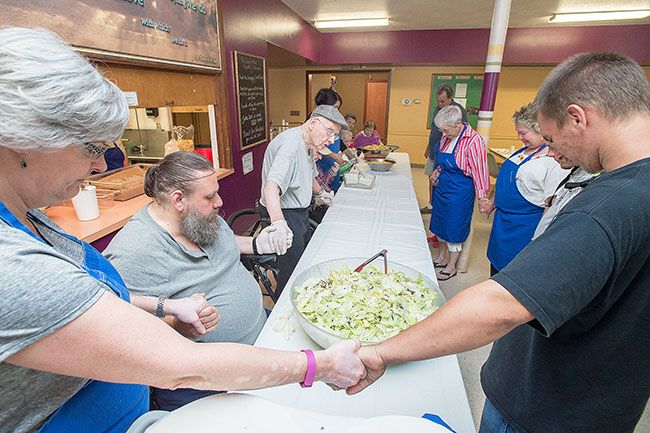 Marcus Larson/News-Register##Before the start of dinner, the Prestige volunteers and soup kitchen staff hold