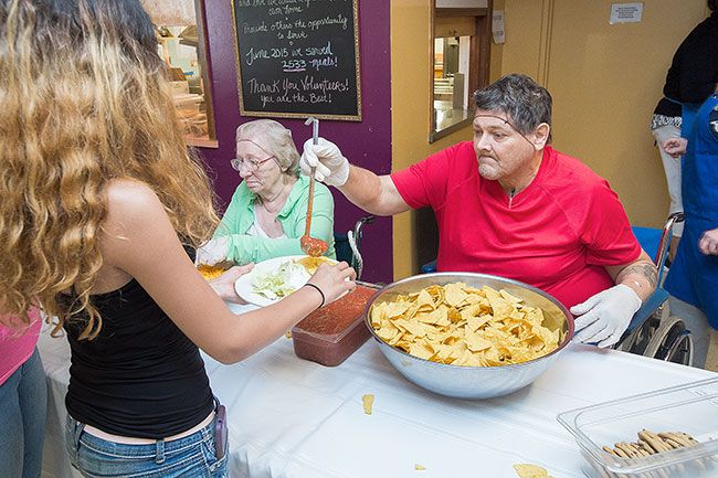 Marcus Larson/News-Register##Prestige volunteers Bruce Brown gives salsa and
