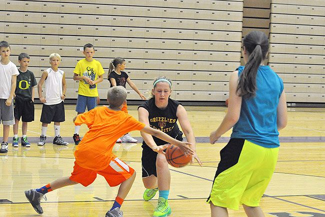 Robert Husseman/News-Register Taylor Reiman, 13 and of Yamhill, attempts a pass while Tate Reese, 11 and of Beaverton, defends during the High Five Basketball Camp at Linfield College.