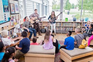 Marcus Larson/News-Register file photo##Joshua Humlie, left, Manuel Humlie and Bethany Blanchard of We Three perform music for the children in the Sue Buel Elementary School library.