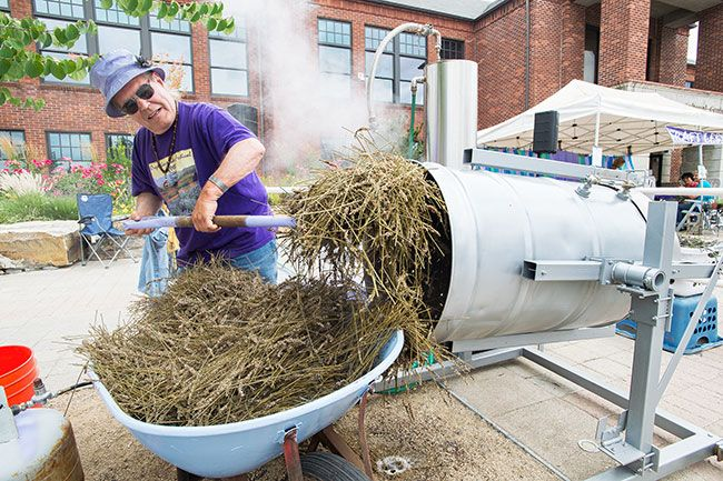 Marcus Larson/News-Register##Lavender oil maker Butch Bochart empties his vat of used up lavender plants.