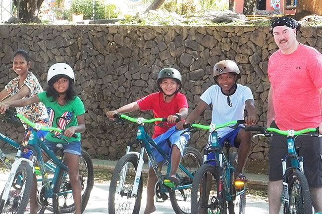 Submitted photo##In the Philippines, Larry Vollmer, right, prepares for a bike riding session with youngsters who are looking for permanent homes. Vollmer is an ambassador for Holt International, an adoption agency.