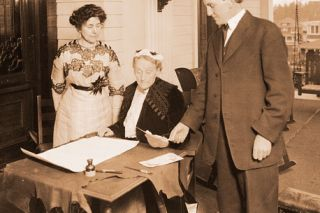 Image: Oregon Historical Society##Gov. Oswald West and Dr. Viola M. Coe look on as Abigail Scott Duniway, center, signs the Equal Suffrage Proclamation in November 1912. In that year, women in Oregon won their right to vote, with West's help.