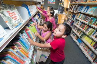 Marcus Larson/News-Register##Alexander Ponce and other children look through rows of books while checking out the McMinnville Public Library Bookmobile. The library visits the Villa del Sol apartments each Tuesday.
