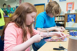 Marcus Larson/News-Register##During activity time at the Carlton Free Lunch program, Ruth Rorabaugh and Kali Sivula work on creating duct tape wallets. Yamhill-Carlton schools serve both breakfast and lunch.