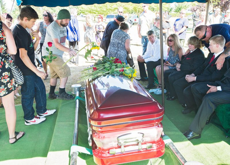 Marcus Larson/News-Register##Mourners place flowers on the casket of Jake Coshow-Wright near the end of the graveside ceremony in his honor Saturday afternoon.