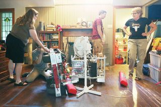 Rockne Roll/News-Register##From right, Nerd Herd robotics team coach Alicia Eagen looks on as Max Kuhn, Meira Lee and Jessica Johnson work on one of the team s robots at Eagan s home in McMinnville.