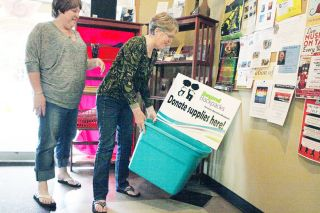 Rockne Roll/News-Register##Maria Mihm, left  and her mother, Celia Kaleta, place a donation bin for Beyond Backpacks at Cornerstone Coffee Roasters in McMinnville on Tuesday. Community members may donate school supplies or cash to the program, which expects to serve 900 children this year.