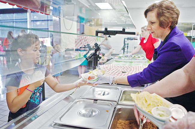 Rockne Roll/News-Register##Rep. Suzanne Bonamici  hands a plate of nachos to 7-year-old Emma LaRon at Newby Elementary School during the summer lunch program. Bonamici, who visited Tuesday, said she supports healthful meals.