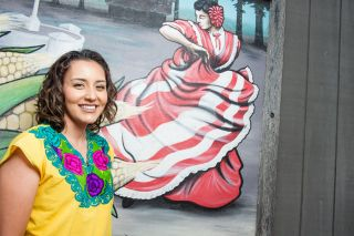 Miriam Vargas Corona, executive director of Unidos Bridging Community, stands with a mural of Mexican folk dancers in Dayton. Rusty Rae/News-Register##She danced with her church group as a child and still remembers the steps when the music plays.
