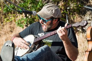 Marcus Larson/News-Register##Musician Konrad Wert, who performs under the moniker Possessed by Paul James, shreds the banjo and kicks his heels up onstage at the 6th annual Wildwood MusicFest & Campout on Saturday at the Roshambo Art Farm.