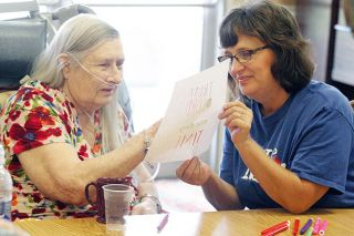 Rockne Roll/News-Register##Jeanne Weirich, right, of Church on the Hill helps 86-year-old Geneva Schroerfer with a coloring project at Life Care Center of McMinnville during the church's Serve Mac service day last year.