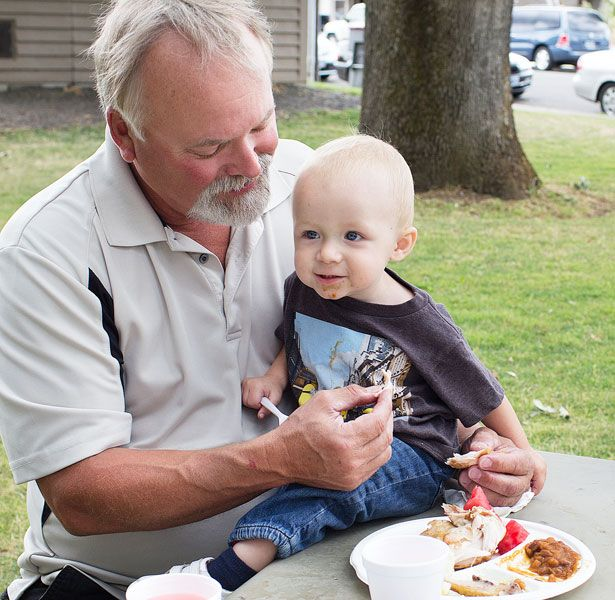 Michaela Fujita-Conrads/News-Register##Robert May feeds grandson Parker May at the Dayton Old Timers Chicken Barbeque on July 26.