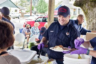 News-Register file photo##Dean Wegner serves potato salad last year during Sunday's chicken barbecue in the park.