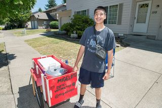Marcus Larson/News-Register##Miguel Lozano,  a sophomore at McMinnville High School, worked with his dad to build a cart from which he could sell his elotes.