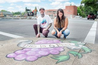 Rusty Rae/News-Register##Jesse McFerran and Natalie Fletcher were commissioned to paint social-distancing reminders on Third Street.