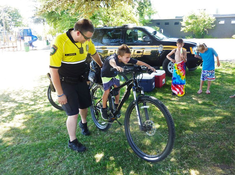Starla Pointer / News-Register##With help from Officer Tim Jordan, 6-year-old Tanner Rauch checks out one of the Carlton police department s new patrol bicycles. Officers will be able to interact with kids more on the bikes, they said.