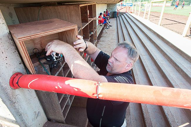 Marcus Larson/News-RegisterJoe Miglioretto adjusts a camera in the visitors  dugout at Volcanoes Stadium in Keizer.