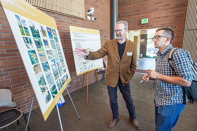 Marcus Larson/News-Register##Jack Chapman, right, chats with Peter Reedijk, design director for Sheridan company Sea Reach, about what designs best represent McMinnville if used for signage.