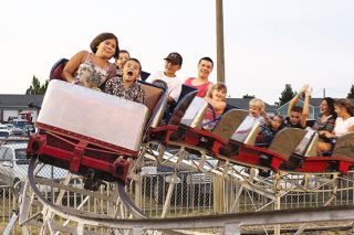 Michaela Fujita-Conrads / News-Register##Jeremiah and Mariah Lotseeit excitedly ride a roller coaster. Hot weather did not deter crowds from the Yamhill County Fair and Rodeo.