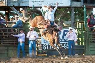 Marcus Larson/News-RegisterCowboy Johnny Espeland holds on for dear life during his saddle bronc ride.
