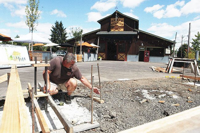 Rockne Roll / News-Register##Granary District General Manager Kelly McDonald preps the site of a new outdoor stage. Community members will gather Saturday, Aug. 15, to raise the structure.