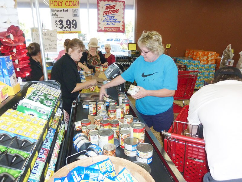 Starla Pointer / News-Register##Cindy Shultz unpacks the carts she filled with ravioli, chicken and other