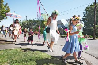 Rockne Roll/News-Register##Sprites of all ages parade along Baker Street toward Hopscotch Toys. Incahoots, a plant, flower and gift shop, hosts the annual Flower Fairy Celebration for children.