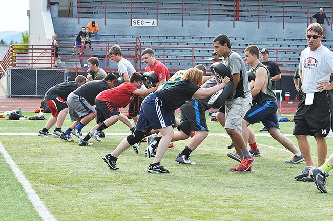 Robert Husseman/News-RegisterMcMinnville High School linemen absorb the blocks of kids camp participants on Thursday.