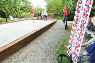 Starla Pointer / News-Register##As Hillside residents play, bocce points add up on a scoreboard at one side of the new court. Residents enjoy the fun of bocce, as well as the challenge of knocking their neighbors' balls away from the target.