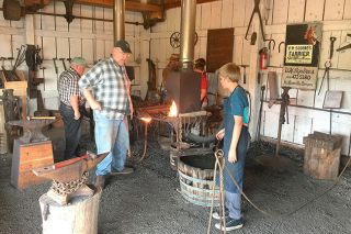 Submitted photo##Ike Bay, Dan Bower and other volunteer blacksmiths teach their craft to youngsters at the Yamhill Valley Heritage Center. The smiths will demonstrate their work at Harvest Fest this weekend.