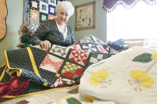 Rockne Roll/News-Register##Priscilla Heinzman shows some of her prize-winning quilts in her Dayton home. She, her mother and her sisters inspire one another to sew and make crafts.