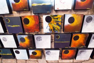 Marcus Larson / News-Register##Some of the 400 ecliipse paintings created by McMinnville artists John Stromme. Downtown businesses are stocked with eclipse souvenirs for an influx of visitors this weekend.