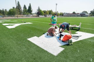 Marcus Larson/News-RegisterConstruction workers lay down lettering on the artificial turf surface in the north end zone of Gubser Field, home of Dayton High School football.