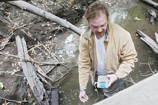 "Rockne Roll / News-Register##Luke Westphal, executive director of the Greater Yamhill Watershed Council, checks the calibration of a water temperature sensor in Cozine Creek, south of downtown McMinnville. ""Stream temperature can be considered a pollutant,"" he said."
