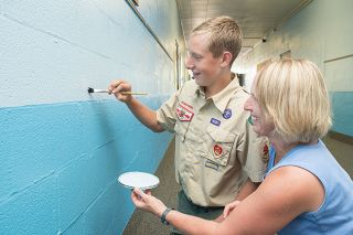 Marcus Larson / News-Register##In the halls of St. James School, Cole Stritzke applies some final touch-up paint with assistance from his