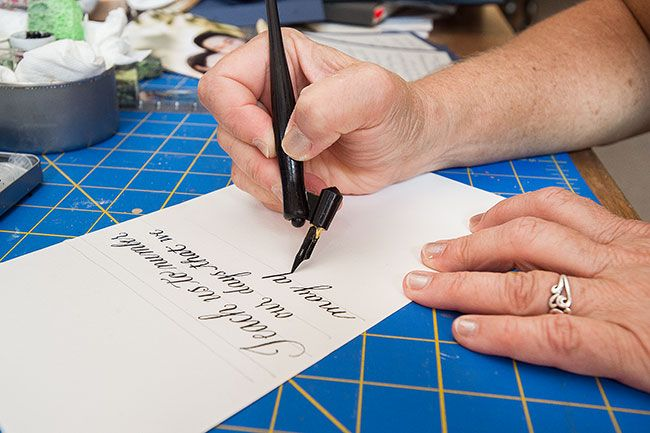 Marcus Larson/News-Register##Newby uses an oblique calligraphy pen that allows her to more easily apply precise amounts of pressure to create thinner or wider strokes.