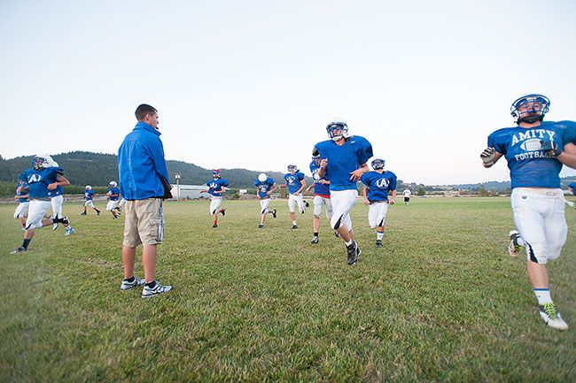 Marcus Larson/News-RegisterJustin Amaya leads Amity football players through drills in a fall practice Friday.