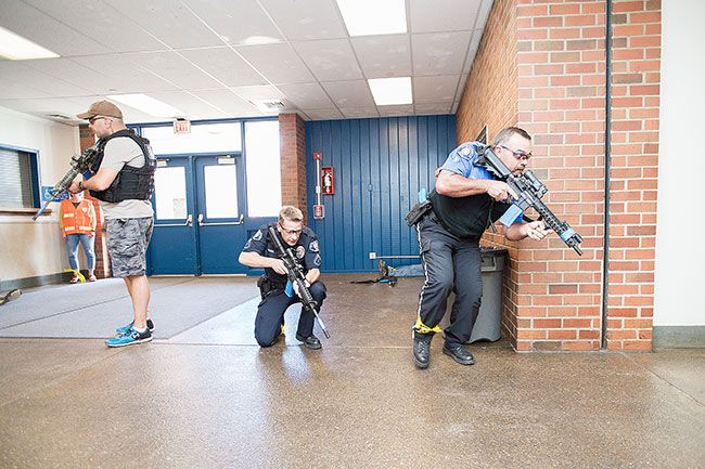 "Marcus Larson / News-Register##McMinnville police officers conduct an ""active shooter"" training at Patton Middle School last Monday. The McMinnville School District's