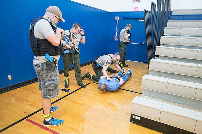 Marcus Larson / News-Register##Sheriff's deputies corner and handcuff the second shooter, played by Police Cheif Matt Scales, inside the Patton Middle School gym. Police conducted a training Monday simulating a shooter at the school.