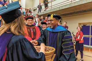 Submitted photo##President Miles Davis talks with Linfield students as they pick up symbolic acorns following the college s opening convocation.