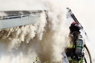 Rockne Roll/News-Register##A firefighter works to gain access to the smoldering attic of a house fire on Southwest Alexandria Street in McMinnville on Friday, Aug. 26.