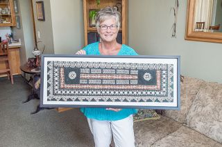 Marcus Larson / News-Register##Sue Kinion holds a precious souvenir she brought back to McMinnville from the medical mission: A tapa cloth, made from mulberry leaves that are beaten and dried, then painted with traditional Fijian designs.