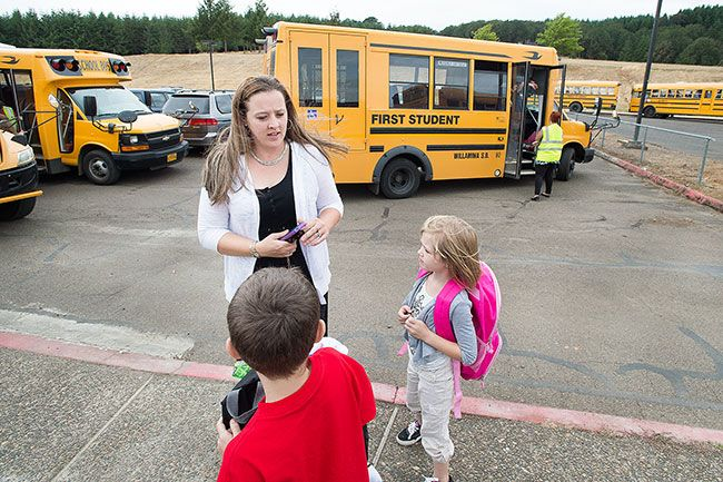 Marcus Larson/News-Register##Sarah Norwood, new principal of Willamina Elementary School,  helps students find their assigned buses at the end of the day.