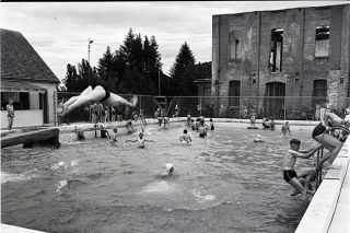 ##Youngsters dive and frolic in the concrete pool on Star Mill Way in 1947, with the old mill still standing in the background. The pool was built in 1934 with help from the Works Progress Administration. Swimmers loved it, despite the cold water.