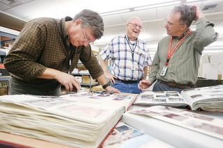 Rockne Roll/News-Register##Evergreen Aviation and Space Museum Curator Terry Juran, left, and volunteers Allen Herkamp and Kirk McFarland pore over photo albums that belonged to Arlene Johnsen, a flight attendant killed in the explosion of TWA Flight 800 in 1996.